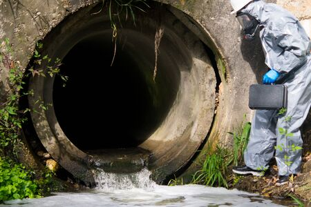 scientist in protective clothing, with a suitcase enters the drain pipe