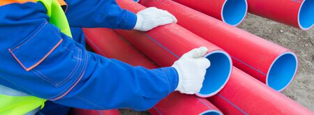 worker's hands, in white gloves, against a background of red plastic pipes stacked on top of each other, close-up