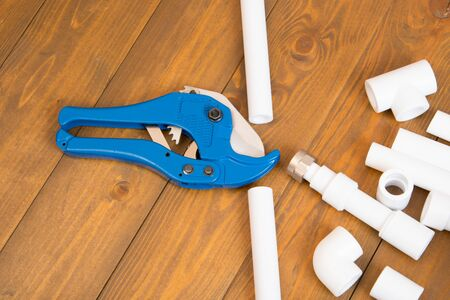 blue scissors for cutting plastic pipes, next to the corners and adapters for them, on a wooden background