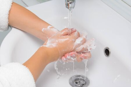 in the bathroom, against the background of a white sink, the child lathers the palms of his hands and washes them under water from the tap, close-up