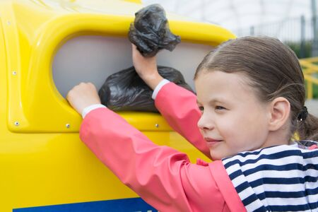 girl in a pink jacket, throwing out a black bag with garbage, in a container, close-up