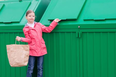 a cheerful girl in a pink jacket, carries a paper bag, in a green garbage container to throw it away, there is a place for the inscription