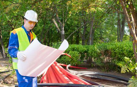 l'ingénieur tient un paquet de papier, des schémas de communication pour la pose de tuyaux en plastique