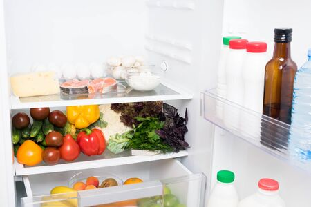 open fridge with vegetables and dairy products inside