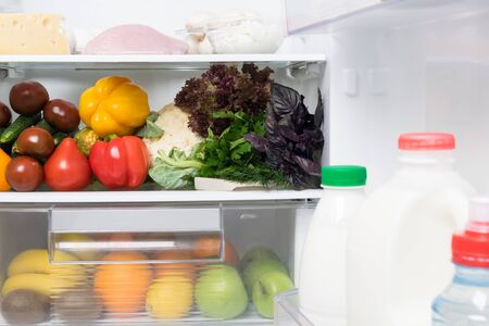 open fridge with vegetables and dairy products inside, front view, close-up