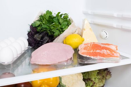 meat, fish and chicken with greens on a shelf in the refrigerator Фото со стока