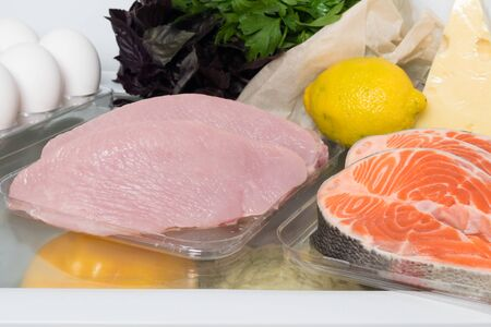 meat, fish and chicken with greens on a shelf in the refrigerator, front view, close-up Фото со стока