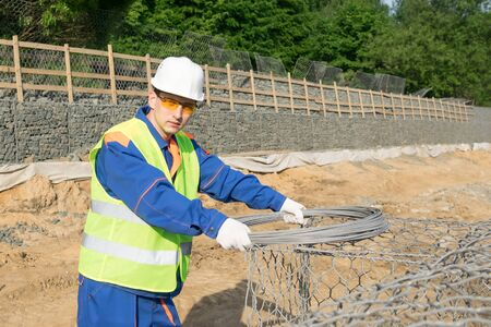 builder holds a skein of wire and looks into the frame Stock Photo