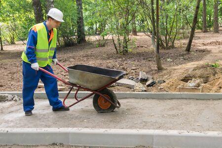 un muratore con un casco porta un carrello vuoto per il trasporto di materiali e ha una gomma a terra