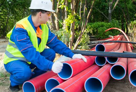 builder in a white helmet, pulls out red plastic pipes stacked on top of each other, there is a place for inscription 版權商用圖片
