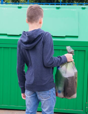 a boy in a blue jumper, carries a full bag of garbage to a container to throw it away, rear view