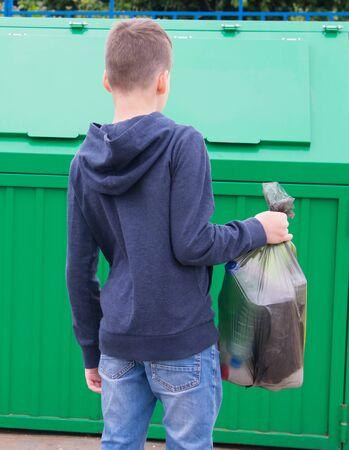 un ragazzo con un maglione blu, porta un sacco pieno di spazzatura in un contenitore per buttarlo via, vista posteriore