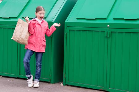 cheerful girl in a pink jacket, carries a paper bag in a green garbage container to throw it away