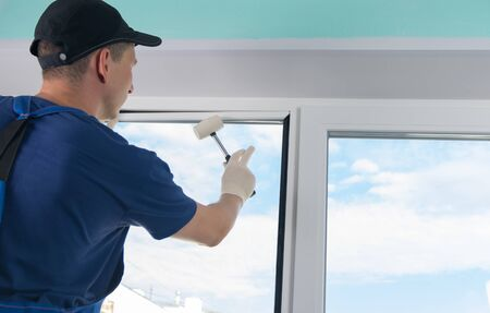 master in protective gloves and a blue uniform, fixes a double-glazed window with a plastic baseboard, hammering it with a rubber mallet, against a blue sky