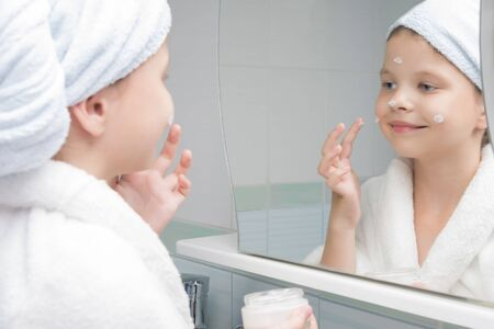 girl in the morning in the bathroom applies cream on her face in front of the mirror