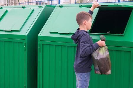 a boy in a blue jumper throws a full bag of garbage into a green container