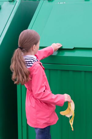 a girl in a pink jacket, throws the skin of a banana in a green garbage container