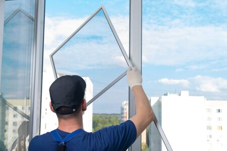 a worker in a blue uniform, rear view, installs a mosquito net in a plastic window frame, against the sky