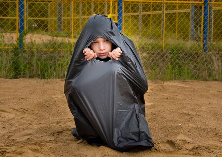 a child sits in a black garbage bag on the sand, against a yellow mesh background