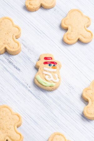 Different shaped cookies on a light gray background with a cheerful snowman in the center