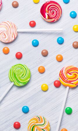 Multi-colored caramel candies on a stick with chocolate dragees on a light background Stockfoto - 134206875