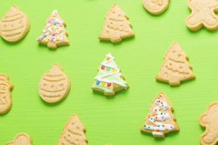 different shape Christmas cookies, Christmas trees with icing on a green background