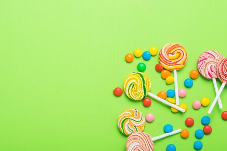 caramel on a stick with colorful jelly beans in the corner of a green background