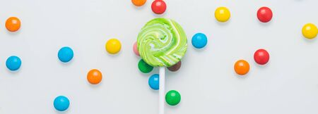 Lollipop on a stick, on a white table and colorful dragees