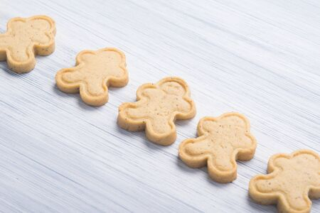 on a light gray background, cookies in the form of snowmen, neatly arranged in a row