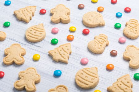 on a light gray background, cookies in the form of a Christmas tree, a snowman, Santa Claus and colorful dragees