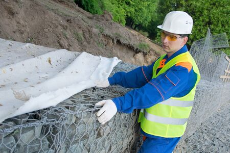 Builder covers the net with stones. Stockfoto