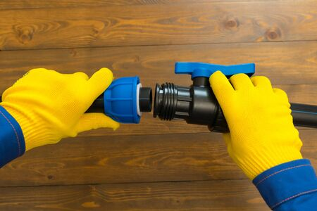 on a wooden background, the hands of a craftsman in yellow gloves, assemble a water pipe for installation Stockfoto - 134207196