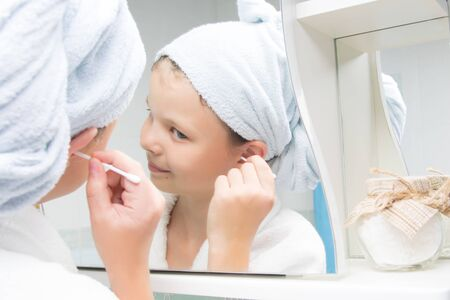 A girl in the bathroom, in a white bathrobe and a towel on her head, cleans her ears with a cotton swab, looking in the mirror Stockfoto