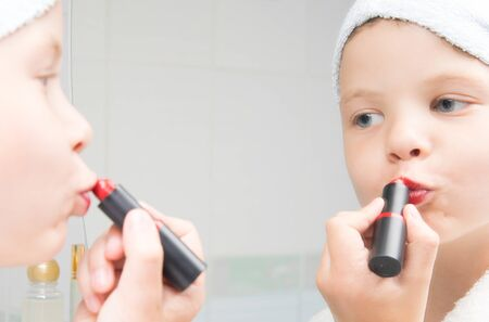 close-up, a girl with a towel on her head, looks in the mirror and paints her lips with red lipstick Stockfoto