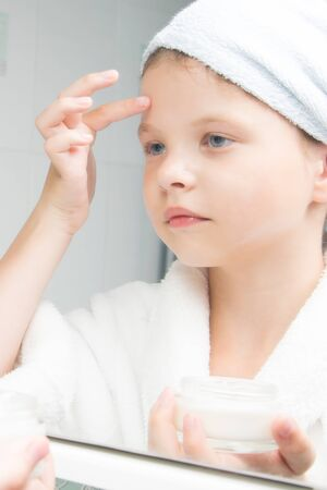 a girl in a white coat and a towel on her head, holds a jar of cream in her hand and puts it on her face