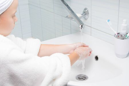 in the bathroom, a girl in a white bathrobe and a towel on her head, washes off soapy hands with tap water Stockfoto - 134207287