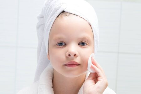 baby girl, in a white robe and towel on her head, cleans her face with a cotton swab, close-up, against the wall in the bathroom Stockfoto - 134207290
