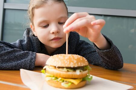 teen girl pulls a wooden stick out of a Burger while sitting at a table, close-up Stockfoto - 134207332