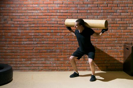 against a background of an orange brick, a man in black uniform is engaged in cross-fit, with a log on his shoulders Stockfoto - 134207351