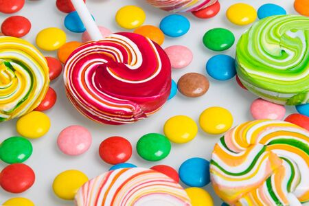 on a white table, close-up, laid out colorful lollipops and jelly beans Stockfoto - 134207471
