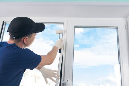 craftsmen in protective gloves, fixes a double-glazed window with a plastic baseboard, hammering it with a rubber mallet, against a blue sky