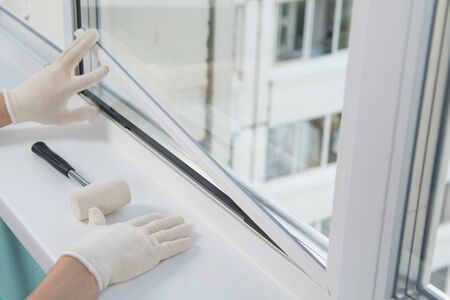 the hands of the worker, install a double-glazed window in the plastic frame of the window, fixing it with a rubber mallet Stockfoto - 134207482