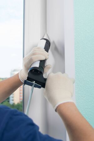 master in protective gloves, fills the gap with silicone to seal the installation of a plastic window, close-up Stockfoto