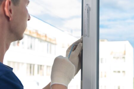 worker adjusts the plastic window with a key, close-up