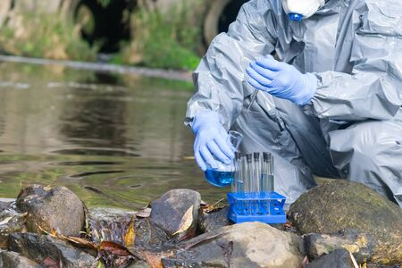 scientist in a protective suit and gloves, pour blue liquid from a test tube into a flask, against the background of the river Stockfoto - 134207501