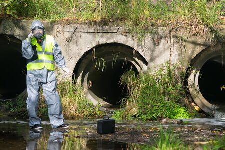 a specialist in a gray protective suit and mask, on a pond, calls on a mobile phone to the management to report the results of the study, against the background of a sewer pipe Stockfoto - 134207525