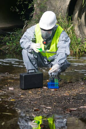 a scientist in a gray protective suit, helmet and mask, on a pond, pours a green liquid from a flask into a test tube, for research Stockfoto - 134207534