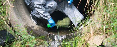 close-up, a terrorist in a protective suit, pours a liquid with poison, for infection, in the drain pipe Stockfoto