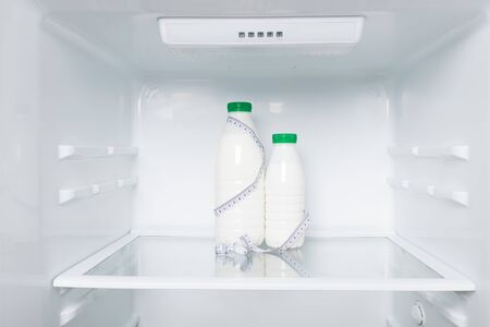 concept milk and meter  for measuring body size on the background of the refrigerator, milk diet Stockfoto - 134207734
