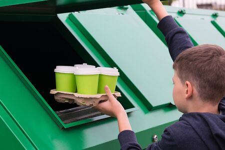 boy puts used paper cups in the trash after lunch Stockfoto - 134207769